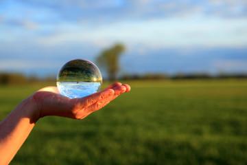 Szklana kula na dłoni w świetle zachodzącego słońca.