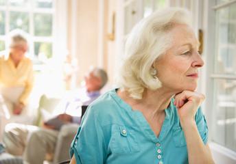 Senior woman looking through window in nursing home