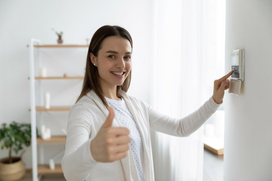 Smiling young woman use turn on smart home control panel on apartment wall, recommend good quality service show thumb up, happy millennial female client switch fire alarm or house security system