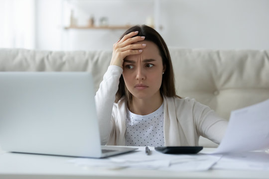 Confused young woman calculating household expenses, have problems paying bills online, unhappy millennial female feel frustrated managing home expenditures finances, troubled with online banking