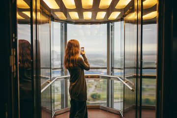 Young woman taking picture while standing in transparent elevator