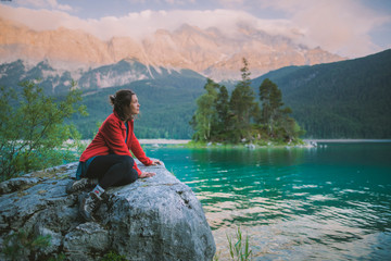 Germany, Bavaria, Eibsee, Young woman sitting on rock and looking at scenic view by Eibsee†lake in Bavarian Alps Wall mural