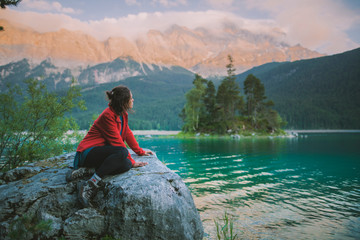 Germany, Bavaria, Eibsee, Young woman sitting on rock and looking at scenic view by Eibsee lake in Bavarian Alps Wall mural