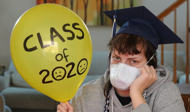 A graduating senior stuck at home in quarantine wears a mask and holds up a sad balloon - graduation for the class of 2020  is not what they had pictured.
