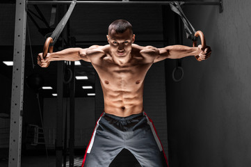 The athlete pulls himself up on the gymnastic rings. The concept of sport and healthy lifestyle.