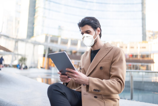 Young man using his tablet outdoor while wearing a mask