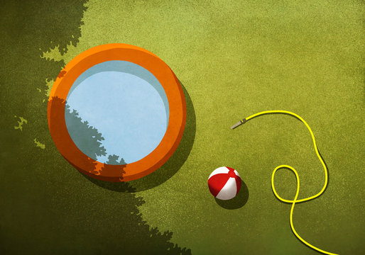 Wading pool, beach ball and hose in sunny backyard