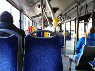 Interior of a city bus with blue seats in Europe.