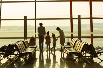 Happy families look outside the lounge at the airport