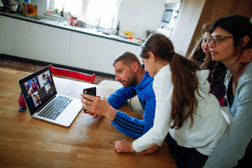 The Perrini family uses a mobile phone and laptop to make a video call to celebrate Easter Monday with their family members during a lockdown, in the small southern historical town of Cisternino