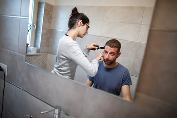 Vanna Angelini shaves her husband Daniele Perrini?s hair in their bathroom at home as hairdressers remain closed, in the small southern historical town of Cisternino
