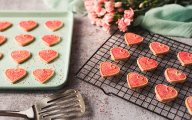 Pink Valentine's day heart cookies cooling on a pan and rack.