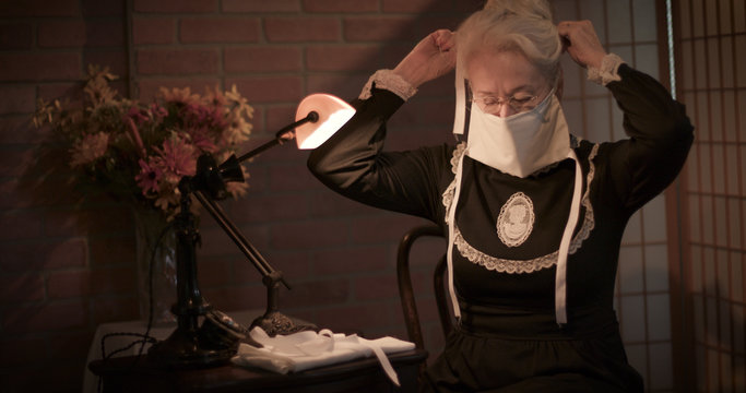 An old woman sitting in her home tries out the face mask she has handmade to wear during the 1918 Spanish Flu pandemic.