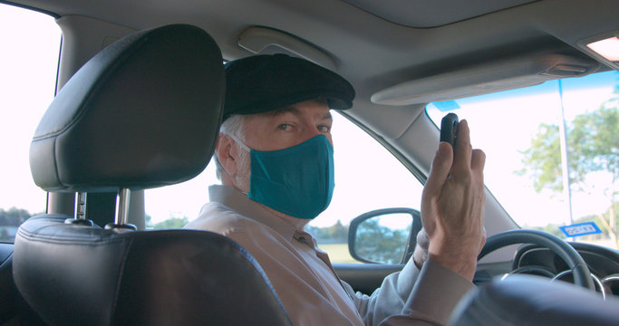 A mature retiree Uber or Lyft ride sharing driver wearing a mask due to COVID19 risks greets his passenger and engages in friendly conversation before starting the ride.