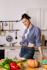Young and beautiful housewife woman cooking in a white kitchen
