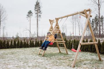 boy sat on a swing swinging outside in his garden in the snow