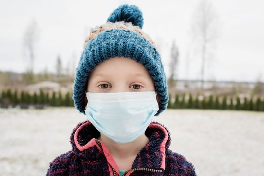 young boy with face mask on protecting himself from flu and virus