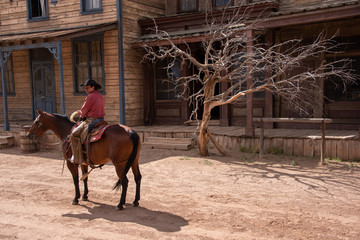 Cowboy riding his horse through an old western town