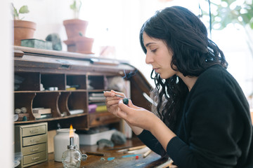 Portrait of female jewler working at home studio with small tools