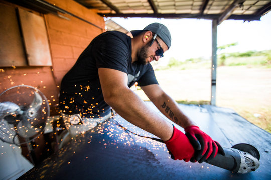 Worker using angle grinder to cut steel.