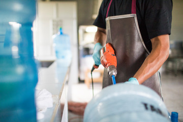 Worker uses a power drill to wash out a drinking water jug for re-use.