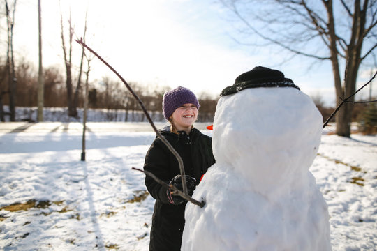 Smiling girl making snowman in winter