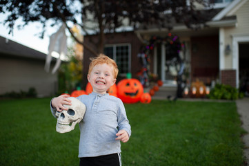 Toddler boy excited about holding skull in front of halloween decor