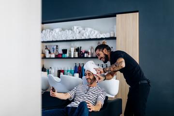 Cheerful males in hair salon having fun during procedures
