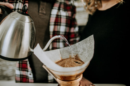 couple prepares coffee by pouring hot water over grounds and filter