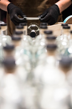 Applying labels to liquor bottles at a distillery.