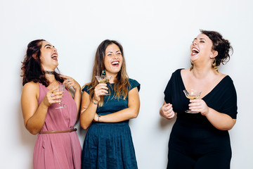 Laughing trendy women celebrating with cocktails