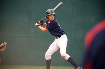 Young baseball player in batters box ready to swing