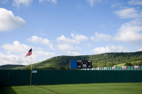 Baseball outfield fence and rolling hill with scoreboard and American Flag