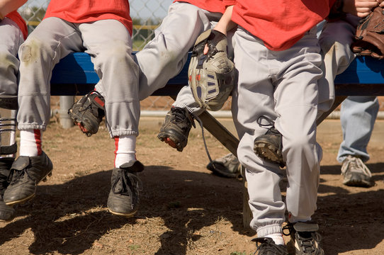Boys legs intertwined on a baseball bench