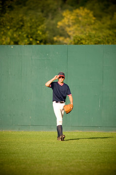 Young outfielder adjusting his sunglasses on baseball field