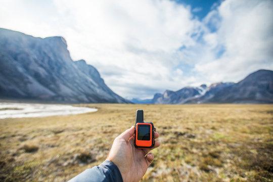 Adventurer holds mini GPS and satellite safety communication device.