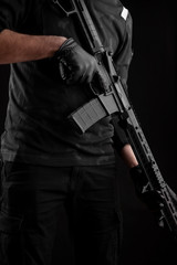 Fototapeta A man holds an automatic carbine on a dark back. A fighter in dark clothing with a weapon in his hands. Poster concept for police, security or military.