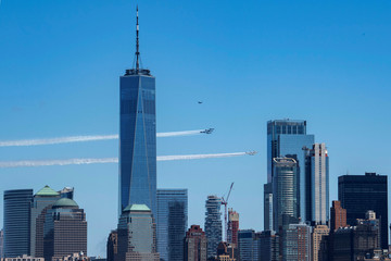 The U.S. Navy Blue Angels and U.S. Air Force Thunderbirds demonstration teams participate in a flyover