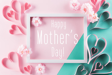 Happy Mother's Day, Women's Day or Valentine's Day greeting concept. Pastel Pink Colours Background with picture frame, handmade heart and blossom flowers flat lay patterns.