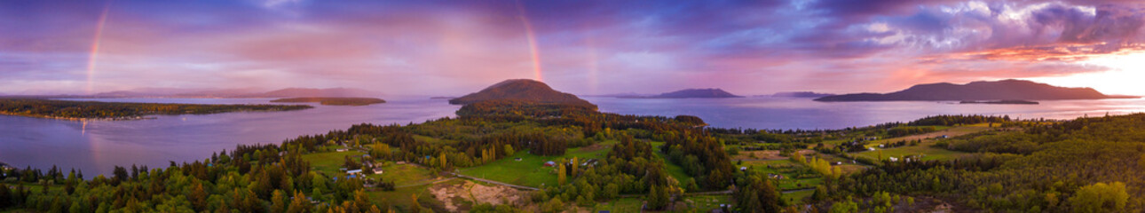 Wall Mural - Aerial View of a Beautiful Island Sunset With a Gorgeous Rainbow. Springtime brings dramatic sunsets and colorful rainbows but hardly ever both. This is Lummi Island, Washington in the Salish Sea.
