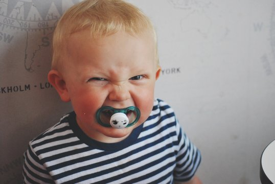 Portrait Of Angry Baby Boy Sucking Pacifier At Home