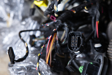Close up of the engine control unit of the car, multicolored wires plug, contacts  - a wiring of a truck car.  Electrical communication, wires in an old car
