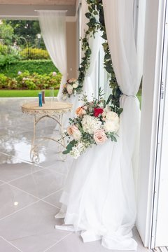 Vertical shot of a wedding venue with white curtains and beautiful flowers