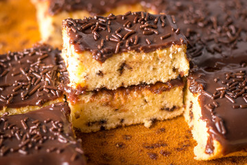 Pedaços de Bolo Formigueiro com Cobertura de Chocolate ao Leite e Granulado de Brigadeiro sobre papel manteiga
