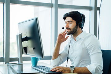 Smiling handsome young male call centre operator with headset.Confident male customer service representative,operator,agent,call centre worker,support staff speaking with head set in modern office