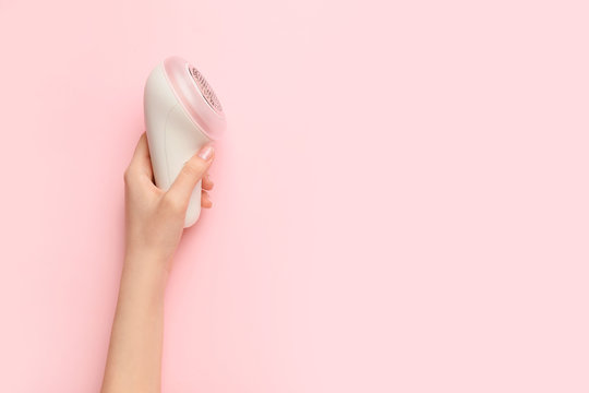Female hand with modern fabric shaver on color background