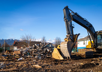 Demolition bulldozer in front of building rubble. Bucket is down, side view. Yellow construction machine with residential buildings and mountains in background.