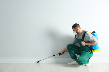 Pest control worker in uniform spraying pesticide indoors. Space for text