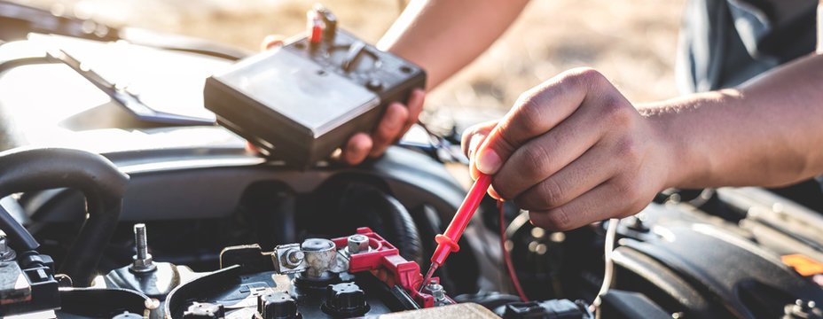 Mechanic repairman checking engine automotive in auto repair service and using digital multimeter testing battery to measure various values and analyze, Service and Maintenance car battery check
