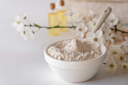 Ceramic bowl with white clay powder on white background. Ingredients for homemade facial and body mask or scrub and fresh sprig of flowering cherry. Spa and bodycare concept.